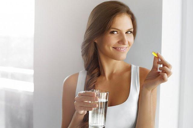 женщина пьет витамны