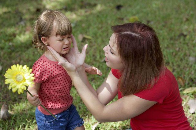 Девочка  плачет возле мамы