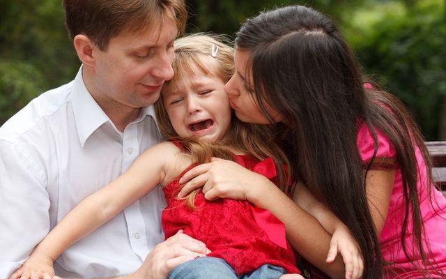Девочка плачет на руках у родетелей