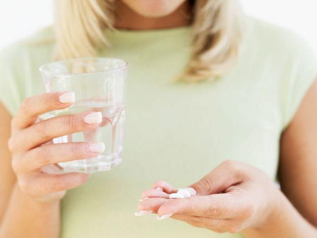 Женщина пьет лекарство