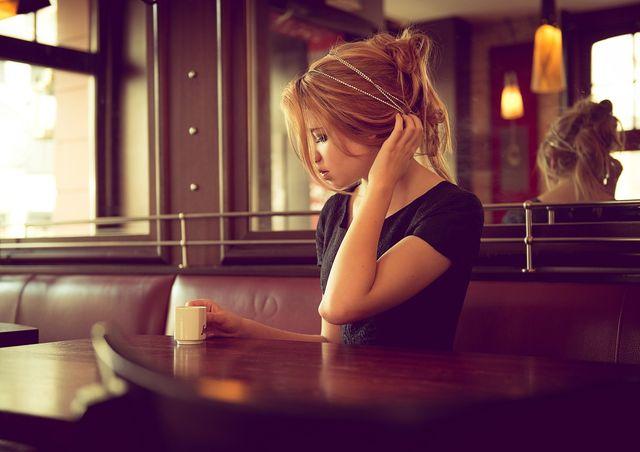 Женщина грустит за столом